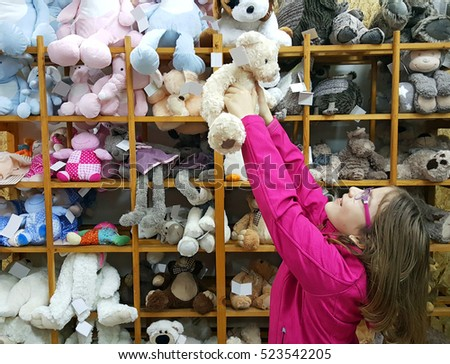 happy little girl play with Teddy bear in store