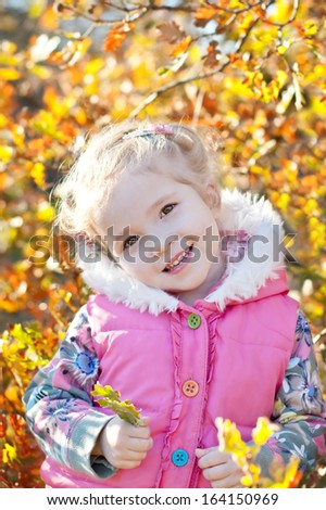 happy little girl playing in autumn woods on the background of yellow leaves
