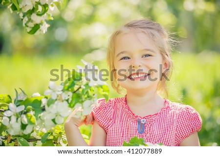 Happy little girl playing in spring apple tree garden - stock photo