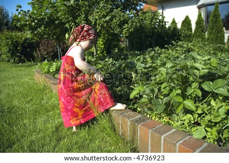 happy little girl playing in the garden - stock photo