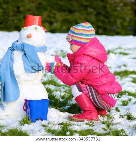 Happy little girl playing in winter. Cute kid making snowman in the garden at the backyard of the house. Child having fun outdoors. - stock photo