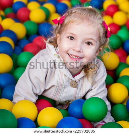 happy little girl playing on colorful balls playground