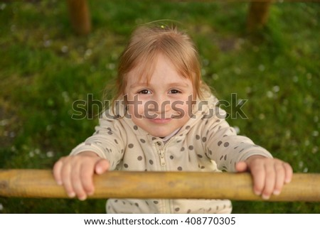 Happy little girl playing on outdoor playground
