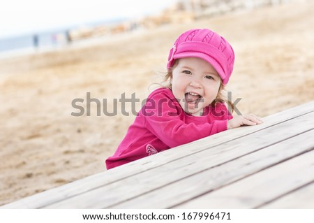 happy little girl playing on the beach in spring time - stock photo