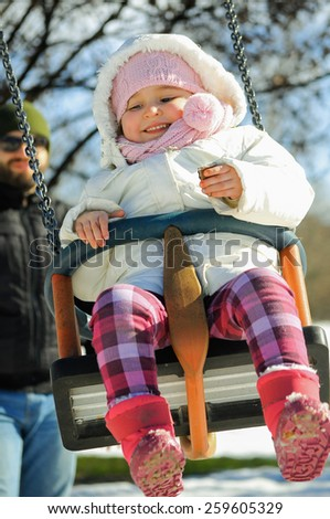 Happy little girl playing on the swing with her father.