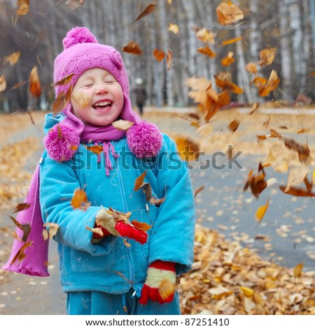 Happy little girl playing with autumn leaves - stock photo