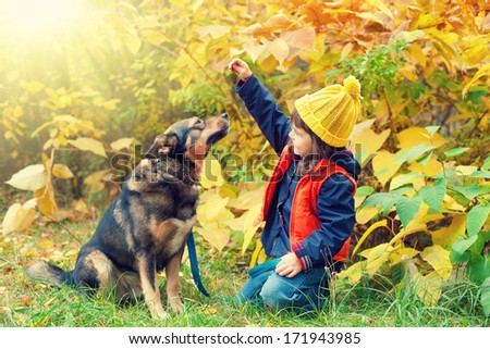 Happy little girl playing with big dog in the forest in autumn - stock photo