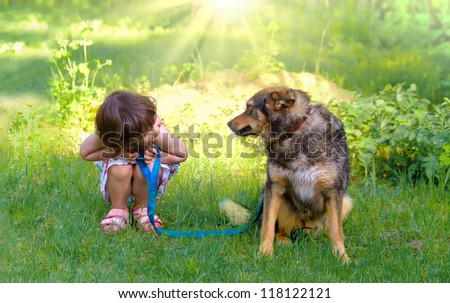 Happy little girl playing with big dog in the garden - stock photo
