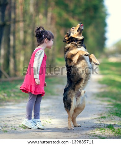 Happy little girl playing with big staying  dog in the forest - stock photo