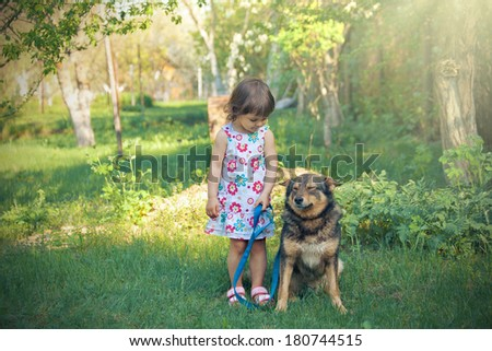 Happy little girl playing with dog in the garden