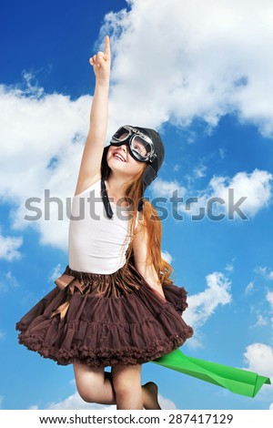 Happy little girl playing with paper airplane - stock photo