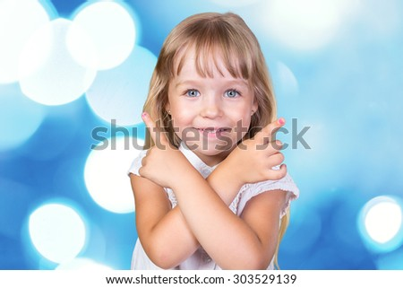 Happy little girl pointing up - stock photo