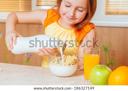 Happy little girl pours milk in cereal flakes for breakfast - stock photo