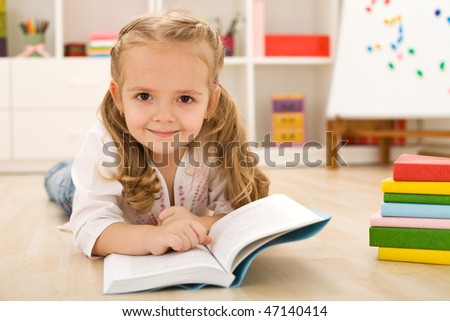 Happy little girl practicing reading laying on the floor in her room - stock photo