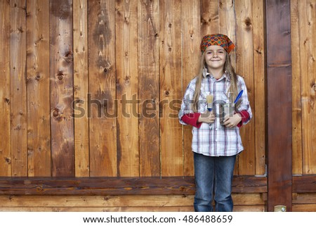 Happy little girl proud to repaint the wood shed - standing in front of wooden plank wall, large copy space