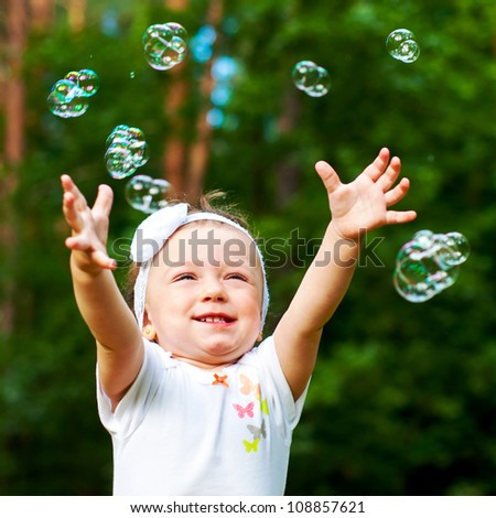happy little girl reaching for bubbles - stock photo