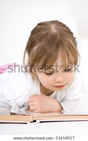 happy little girl reading book - stock photo
