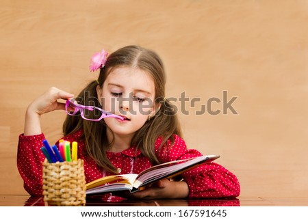 Happy little girl reading book in classroom - stock photo