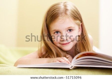 happy little girl reading indoor - stock photo