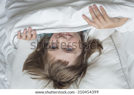 happy little girl resting in a bed