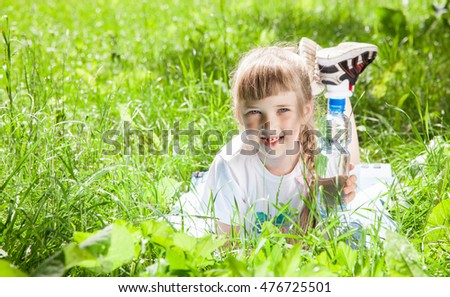Happy little girl resting in the summer park and holding a bottle of water