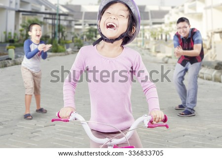 Happy little girl riding bicycle with her dad and brother clapping hands at the back