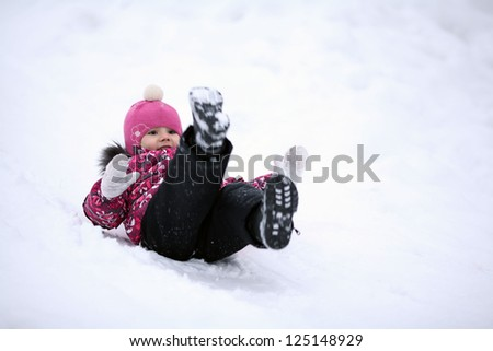 happy little girl riding on icy hill - stock photo