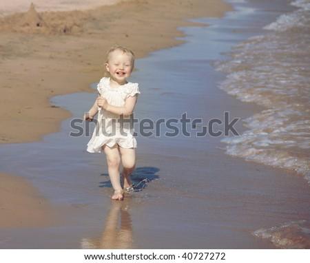 happy little girl run on the beach - stock photo