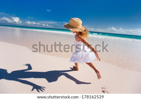 Happy little girl running and jumping at beach - stock photo