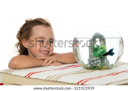 Happy little girl sees a fish that swims in a fishbowl-Isolated on white background - stock photo