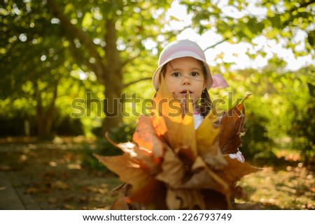 Happy little girl sharing her bouquet of leaves outdoors in autumn park. Happy child playing with leaves. - stock photo
