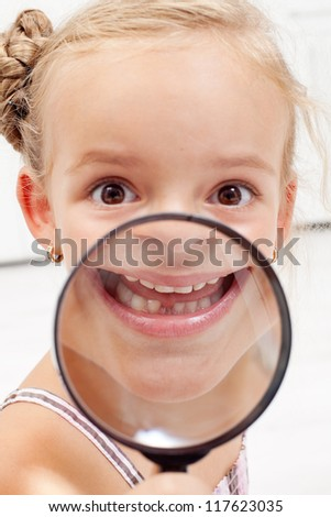 Happy little girl showing missing teeth through magnifier - stock photo