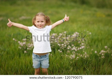 Happy little girl showing thumb us signs outdoors over green grass background - stock photo