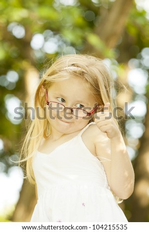 Happy little girl showing thumbs up. Outdoor - stock photo
