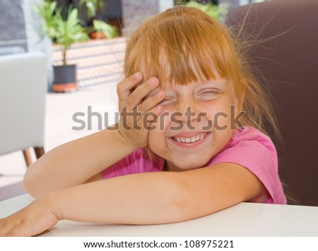 Happy little girl sits at a table - stock photo
