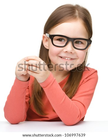 Happy little girl sits at a table and smile while wearing glasses, isolated over white - stock photo