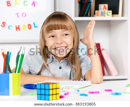 Happy little girl sitting at desk in the classroom, doing homework at the table