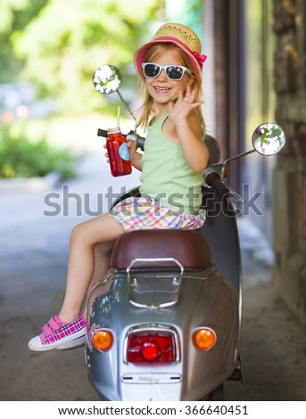 Happy little girl sitting in  a vintage scooter in the street wearing hat and sunglasses drinking juice. Holiday and travel concept