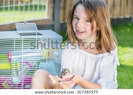 Happy little girl sitting in the backyard with a small hamster in hands - stock photo