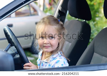 Happy little  girl sitting of car on driver seat holding steering wheel  - stock photo