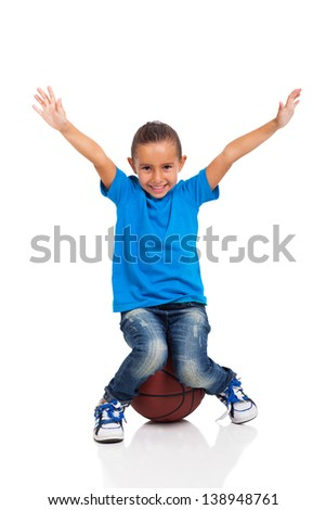 happy little girl sitting on a basketball ball on white background - stock photo