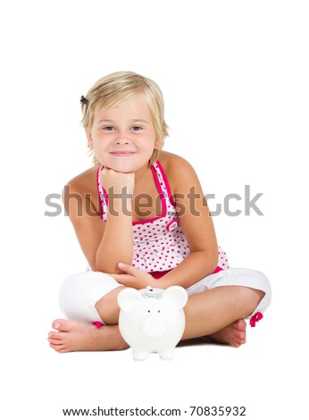 happy little girl sitting on floor with piggy bank - stock photo