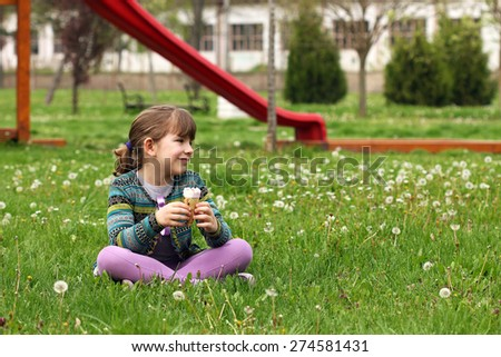 happy little girl sitting on grass with ice cream - stock photo
