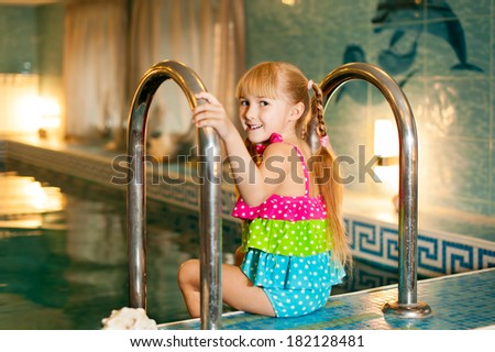 happy little girl sitting on the edge of the pool  - stock photo