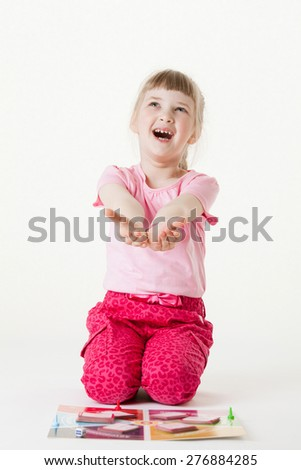 Happy little girl sitting on the floor, reaching out her palms and catching something, white background - stock photo