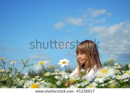 Happy little girl sitting on the meadow