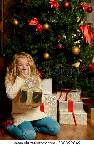 Happy little girl sitting under the Christmas tree with her gift.  - stock photo