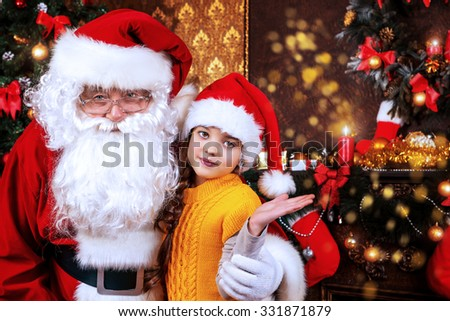 Happy little girl sitting with Santa Claus and rejoice a gift. Christmas decoration.  - stock photo