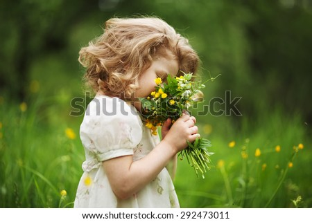 Happy little girl smelling a bouquet of flowers - stock photo