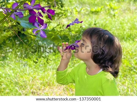 Happy little girl smelling the flower on the tree - stock photo